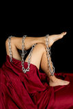 Woman in red sheet legs out chain wrapped Stock Images
