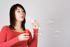 Woman in red shirt blowing out soap bubbles Royalty Free Stock Image