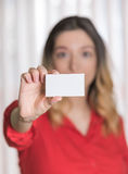 Woman in a red shirt holding up a blank business card Stock Photos