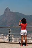 Woman with red shirt photographing Christ the Redeemer from the Sugarloaf Mountain Royalty Free Stock Images