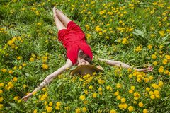 Young woman in red dress is laying on the grass full of yellow flowers. Woman in red shoe dress is enjoying the summer weather royalty free stock image