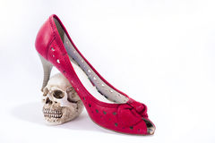 Woman red shoes and small skull. royalty free stock image