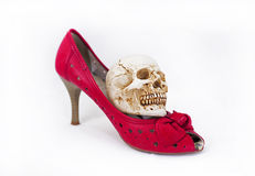 Woman red shoes and small skull. stock photo