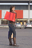 Woman with red shopping bag. In front of a supermarket.Shot with Canon 70-200mm f/2.8L IS USM Royalty Free Stock Photos