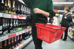 A woman with a red shopping bag chooses alcohol in a supermarket. Selection of products in the supermarket. The choice of wine in the store Royalty Free Stock Photography