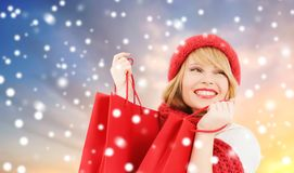 Woman with red shopping bags over snow background. Sale, winter and christmas concept - smiling young woman in red hat and scarf with shopping bags over snow royalty free stock images