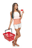 Woman with red shopping basket. Shopping concept. Happy full length woman standing with empty red shopping basket and showing blank credit card, white background Royalty Free Stock Photos