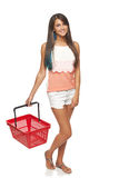 Woman with red shopping basket. Shopping concept. Happy full length woman walking with empty red shopping basket, white background Royalty Free Stock Photos