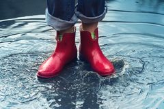 Woman with red short boots standing in a puddle of rain water stock photo