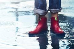 Woman with red short boots standing in a puddle of rain water royalty free stock images