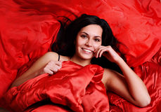 Woman on red silk sheets. A woman laying on a bed with bright red, silk sheets stock photo