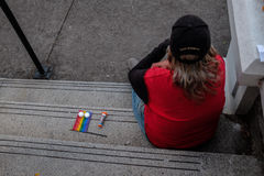 Woman in red sits by tiny flag and candles at LGBT vigil for slain Orlando nightclub victims Royalty Free Stock Photos