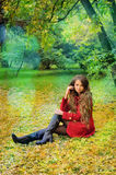 Woman in red sitting in autumn park. Royalty Free Stock Photos