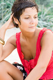 Woman in red sitting on a sand Stock Images