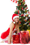 Woman in red sitting under Christmas tree with gifts Stock Images