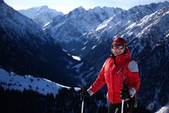 Woman in red on ski slope. In high mountains Stock Images