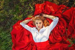 Woman in red skirt lying under the tree Royalty Free Stock Photo