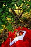 Woman in red skirt lying under the tree Royalty Free Stock Photography