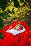 Woman in red skirt lying under the tree Royalty Free Stock Image
