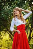 Woman in red skirt standing under the tree Stock Image