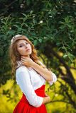 Woman in red skirt standing under the tree Royalty Free Stock Image