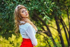 Woman in red skirt standing under the tree Stock Photography
