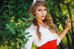 Woman in red skirt standing under the tree Royalty Free Stock Photography