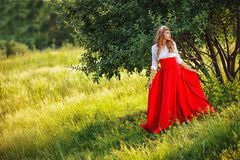 Woman in red skirt standing under the tree Royalty Free Stock Photo