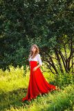 Woman in red skirt standing under the tree Stock Photos