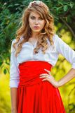 Woman in red skirt standing under the tree Royalty Free Stock Photos