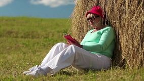 Woman with red smartphone sits near haystack and listens to music stock footage
