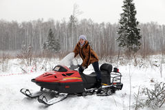 Woman and red snowmobile Stock Images