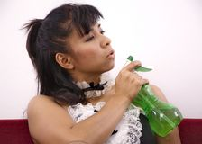 Woman on red sofa holds PVC green spray bottle Royalty Free Stock Photos