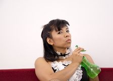 Woman on red sofa holds spray bottle Stock Image