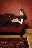 Woman on red sofa serie Stock Photography