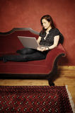 Woman on red sofa serie stock image