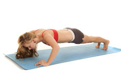 Woman red sports bra doing a pushup Royalty Free Stock Images