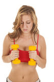 Woman red sports bra yellow weights by chest Royalty Free Stock Image