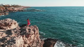 Woman in red standing on the edge of the rocky cliff with hands spread to sides in air. Red dress flapping on wind. Aerial shot of