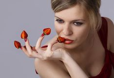 Woman with red strawberries picked on fingertips Royalty Free Stock Images