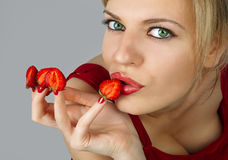 Woman with red strawberries picked on fingertips Stock Photo