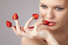Woman with red strawberries picked on fingertips Royalty Free Stock Photography