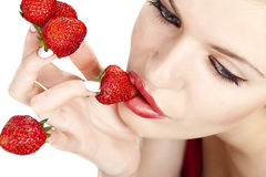 Woman with red strawberries picked on fingertips Stock Image