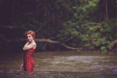 Woman in Red String Spaghetti Strap Dress on Body of Water Near Forest Royalty Free Stock Image