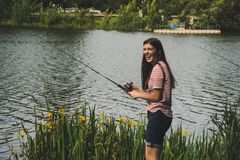 Woman in Red Striped Shirt and Blue Denim Shorts Holding Fishing Rod royalty free stock photography