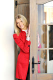 Woman in red suit looks out the door. Beautiful woman in red suit looks out the door royalty free stock photography