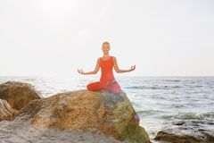 A woman in a red suit practicing yoga on stone at sunrise near the sea. The woman in a red suit practicing yoga on stone at sunrise near the sea Stock Photography