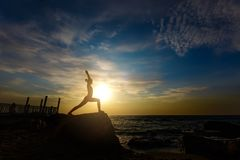 A woman in a red suit practicing yoga on stone at sunrise near the sea. The woman in a red suit practicing yoga on stone at sunrise near the sea Royalty Free Stock Images