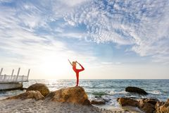 A woman in a red suit practicing yoga on stone at sunrise near the sea. The woman in a red suit practicing yoga on stone at sunrise near the sea Stock Photo