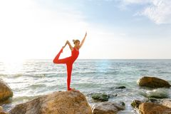 A woman in a red suit practicing yoga on stone at sunrise near the sea. The woman in a red suit practicing yoga on stone at sunrise near the sea Royalty Free Stock Photos